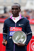 Winner of the Men's race Eliud Kipchoge of Kenya celebrates celebrates with the trophy following the Men's race during the Virgin Money London...