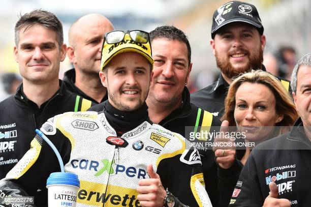 Winner of the Pole Position Switzerland's Thomas Luthi poses with his team after a Moto2 qualifying practice session ahead of the French Motorcycle...
