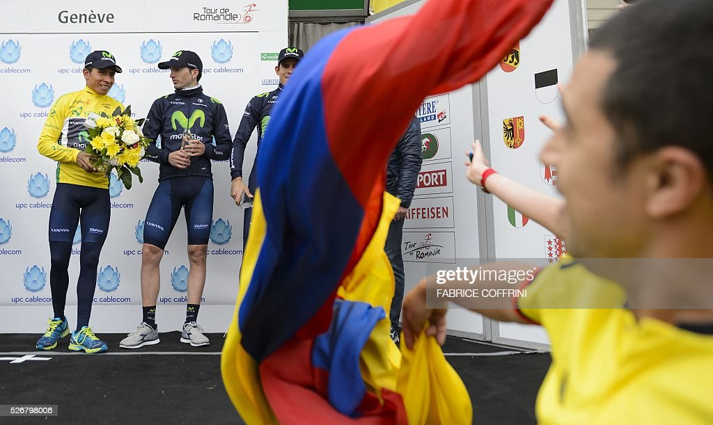 Winner of the race, Colombian Nairo Quintana (L) is congratulated by a fan waving a Colombian flag during the podium ceremony of the last stage of the 70th Tour de Romandie UCI World Tour, a 177,4 km race from Ollon to Geneva, on May 1, 2016 in Geneva. / AFP / FABRICE