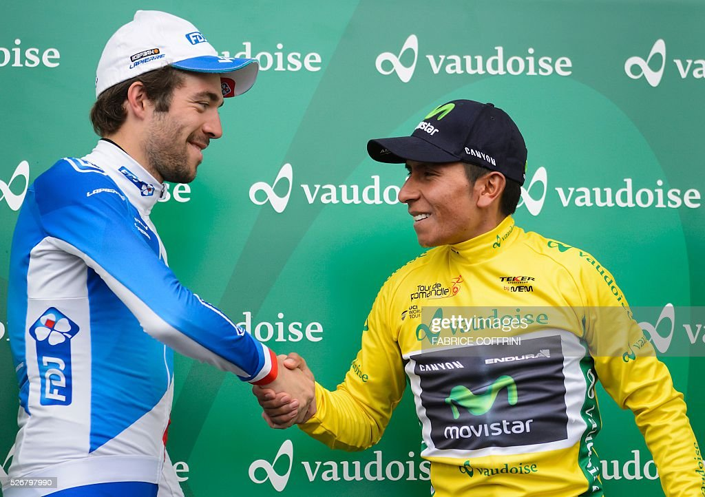 Winner of the race, Colombian Nairo Quintana (R) with his yellow jersey shakes hands to second of the race French Thibaut Pinot during the podium ceremony of the last stage of the 70th Tour de Romandie UCI World Tour, a 177,4 km race from Ollon to Geneva, on May 1, 2016 in Geneva. / AFP / FABRICE