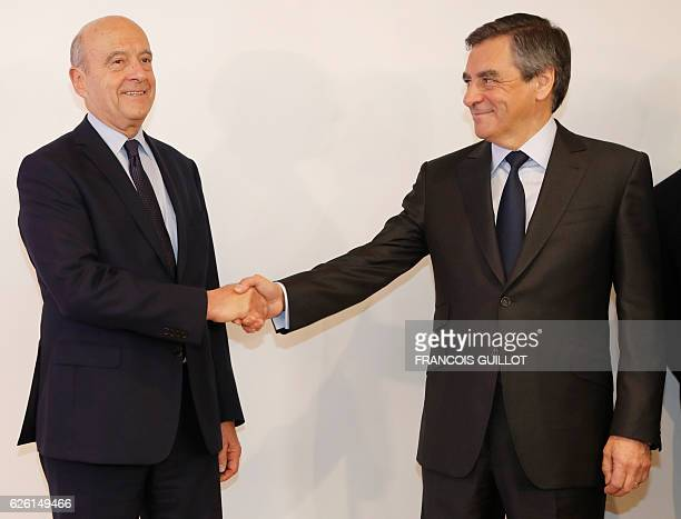Winner of the rightwing primaries ahead of France's 2017 presidential elections Francois Fillon shakes hands with mayor of Bordeaux and defeated...