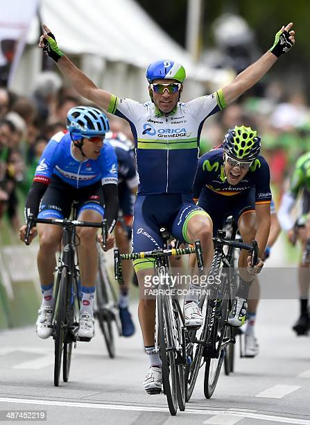 Winner of the stage Switzerland's Michael Albasini of Orica GreenEdge raises his arm in reaction after crossing the finish line ahead of secondplaced...