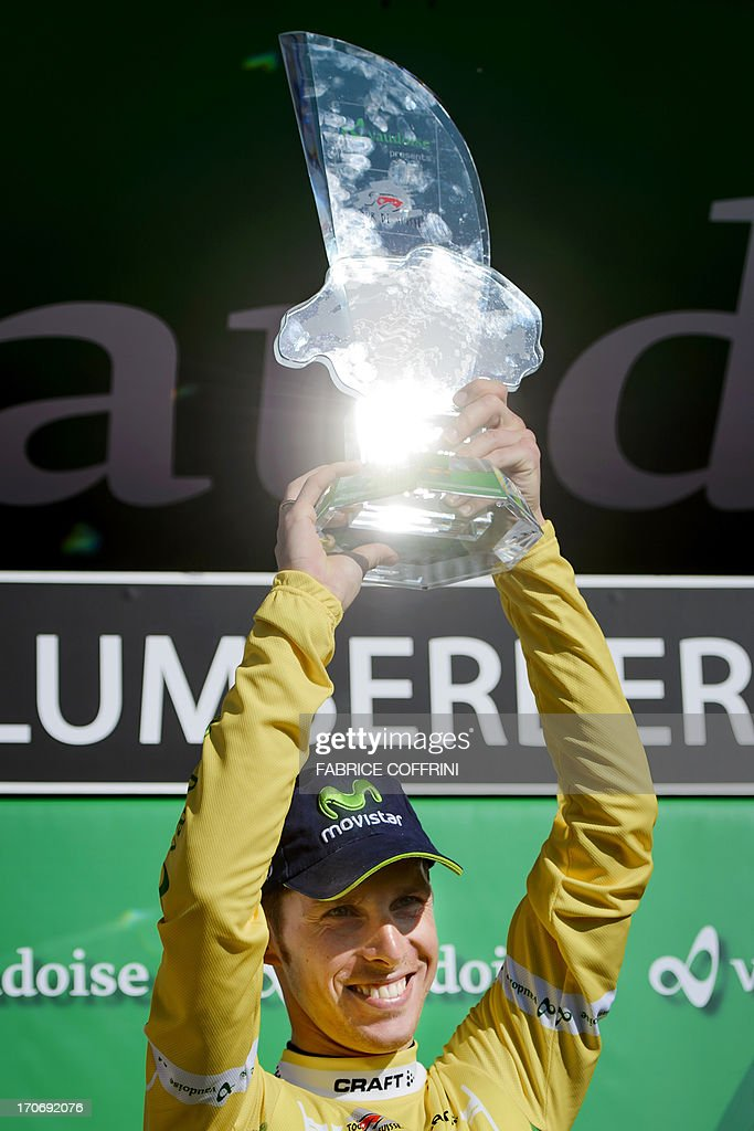 Winner of the Tour of Switzerland, Portugal's Rui Costa of Movistar team raises his trophy on the podium after winning the final stage, a 26,8 km time trial between Bad Ragaz and Flumserberg on June 16, 2013. AFP PHOTO / FABRICE COFFRINI