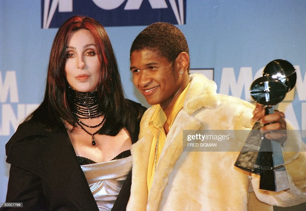 Winner of this year's Billboard Music Awards' Artist of the Year Usher poses backstage with actress Cher in Las Vegas NV 07 December Usher whose...