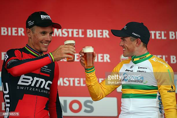 winner Philippe Gilbert of Belgium and BMC Racing Team toasts with third placed Simon Gerrans of Australia and Orica GreenEDGE on the podium after...
