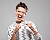 """Portrait of excited young man, raising his fists and screaming with eyes closed. Studio shot, grey background."""