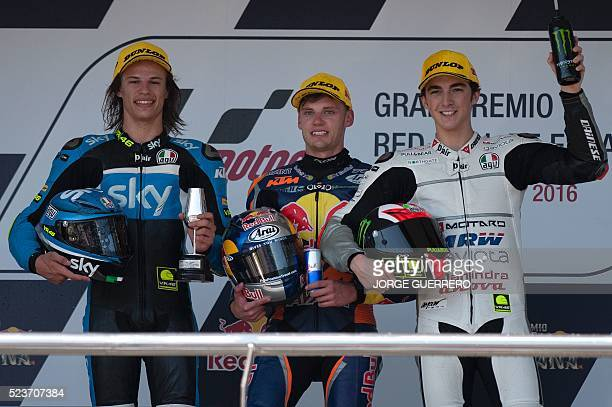 Winner Red Bull KTM Ajo's South African rider Brad Binder celebrates between second placed SKY Racing Team VR46's Italian rider Nicolo Bulega and...
