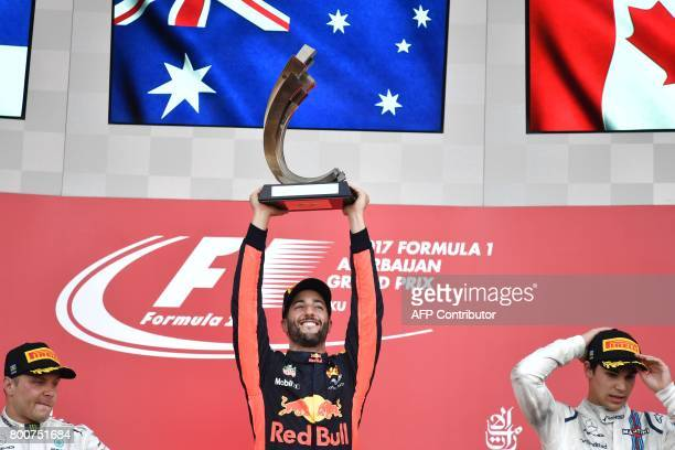 TOPSHOT Winner Red Bull's Australian driver Daniel Ricciardo celebrates with the trophy next second placed Mercedes' Finnish driver Valtteri Bottas...