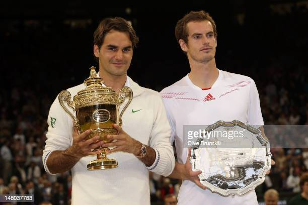 Winner Roger Federer of Switzerland and runner up Andy Murray of Great Britain hold up their trophies after their Gentlemen's Singles final match on...