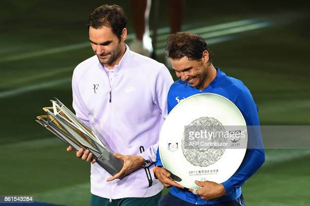 Winner Roger Federer of Switzerland and secondplaced Rafael Nadal of Spain hold their trophies after the men's singles final match at the Shanghai...