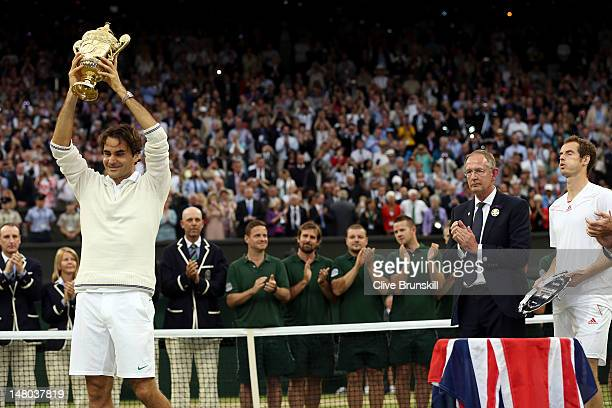 Winner Roger Federer of Switzerland hold up the winner's trophy as runner up Andy Murray of Great Britain looks on after their Gentlemen's Singles...