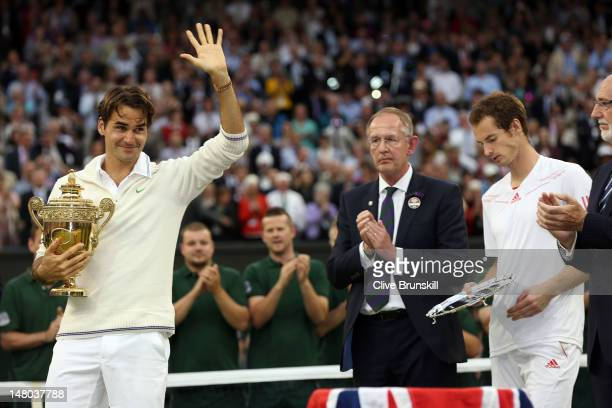 Winner Roger Federer of Switzerland holds his winner's trophy and waves to the crowd as runner up Andy Murray of Great Britain looks on after their...