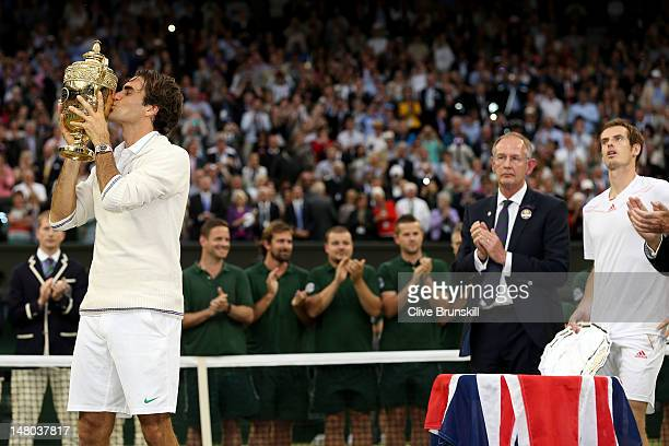 Winner Roger Federer of Switzerland kisses his winner's trophy as runner up Andy Murray of Great Britain looks on after their Gentlemen's Singles...