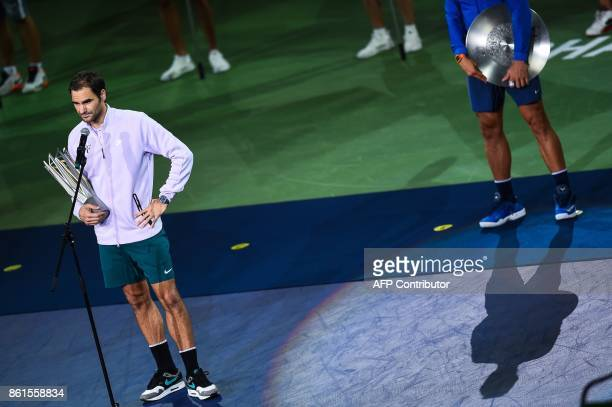 Winner Roger Federer of Switzerland speaks in front of secondplaced Rafael Nadal of Spain as they hold their trophies after the men's singles final...