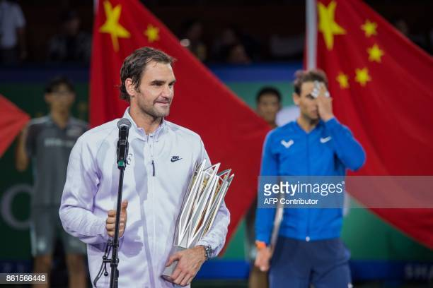 TOPSHOT Winner Roger Federer of Switzerland speaks in front of secondplaced Rafael Nadal of Spain after the men's singles final match at the Shanghai...