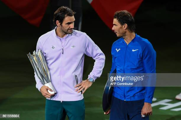 Winner Roger Federer of Switzerland talks to secondplaced Rafael Nadal of Spain as they hold their trophies after the men's singles final match at...