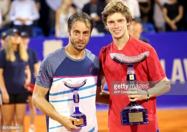 Winner Russian tennis player Andrey Rublev and secondplaced Italian tennis player Paolo Lorenzi pose with their trophies during the prize ceremony...