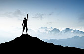 Winner silhouette on the mountain top. Sport and active life concept..