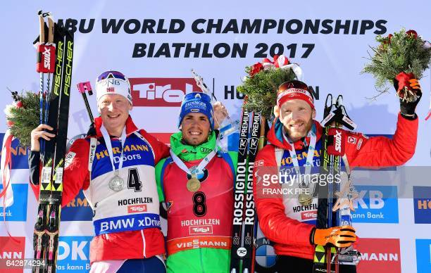 Winner Simon Schempp of Germany celebrates on the podium next to second placed Norway's Johannes Boe and third placed Austria's Simon Eder after the...