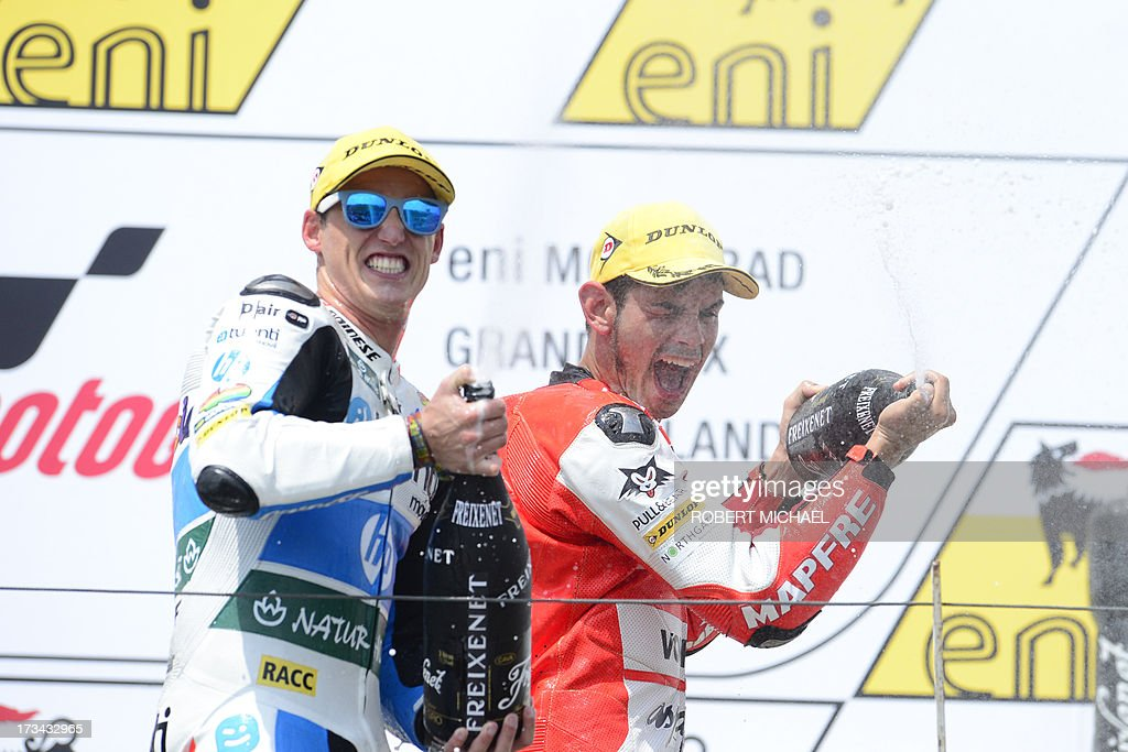 Winner Suter driver Jordi Torres of Spain (R) and Speed up driver Simone Corsi of Italy (L) spray with champagne as they celebrate on the podium after competing in the Moto2 race Grand Prix Germany at the Sachsenring Circuit on July 14, 2013 in Hohenstein-Ernstthal, eastern Germany.