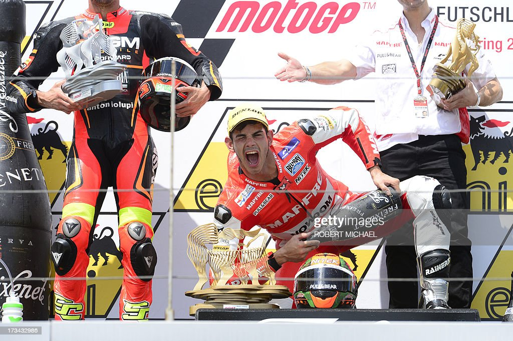 Winner Suter driver Jordi Torres of Spain (C) poses for photographers with his trophy and champagne as he celebrates on the podium after competing in the Moto2 race Grand Prix Germany at the Sachsenring Circuit on July 14, 2013 in Hohenstein-Ernstthal, eastern Germany.