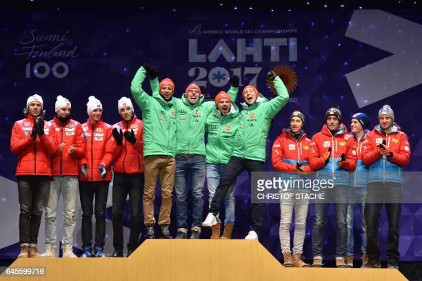 Winner team Germany Bjoern Kircheisen Johannes Rydzek Fabian Riessle and Eric Frenzel celebrate next to Norwegian team placed 2nd and Austrian team...