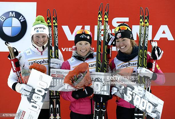Winner US Kikkan Randall 2nd placed Katja Visnar of Slovenia and 3rd placed Sophie Caldwell celebrate on the podium after competing in the Women's...