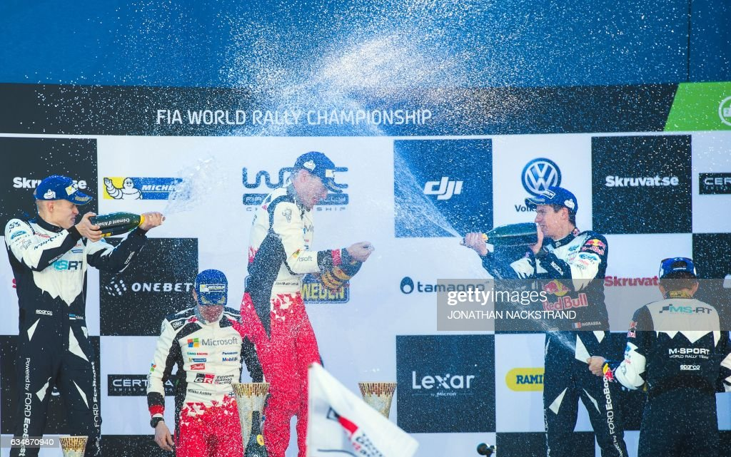 Winners Jari Matti Latvala (C) of Finland and his co-driver Miikka Anttila (2nd L) of team Toyota are being sprayed with champagne by third placed Sebastian Ogier (2nd R) of France and his co-driver Julien Ingrassia (R) of Ford team after the Rally Sweden, second round of the FIA World Rally Championship on February 12, 2017 in Torsby, Sweden. / AFP / Jonathan NACKSTRAND