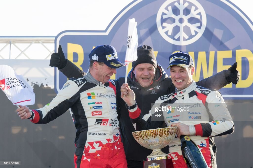 Winners Jari Matti Latvala (R) of Finland and his co-driver Miikka Anttila of team Toyota and their teamm manager Tommi Makinen celebrate during a winners ceremony after the Rally Sweden, second round of the FIA World Rally Championship on February 12, 2017 in Torsby, Sweden. / AFP / TT News Agency / Micke FRANSSON / Sweden OUT