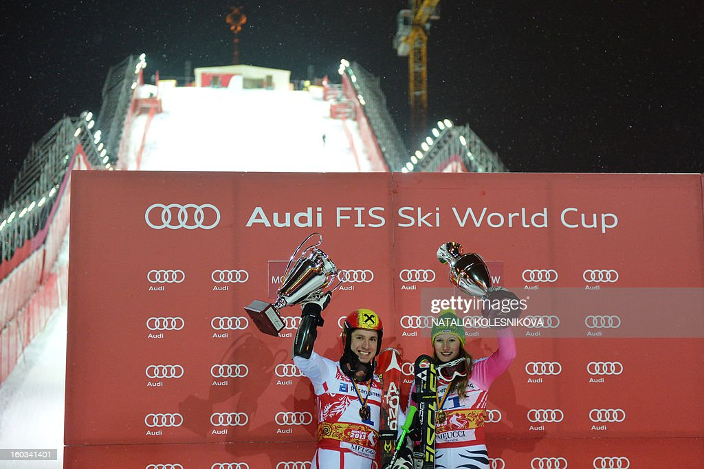 Winners Marcel Hirscher of Austria (L) and Germany's Lena Duerr (R) celebrate on the podium after the FIS Ski World Cup Parallel Slalom city event in Moscow on January 29, 2013. AFP PHOTO / NATALIA KOLESNIKOVA