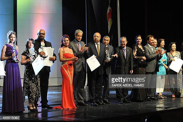 Winners of the best feature film pose with the trophy at the 30th Alexandria film festival closing session on September 15 2014 in Egypt's northern...