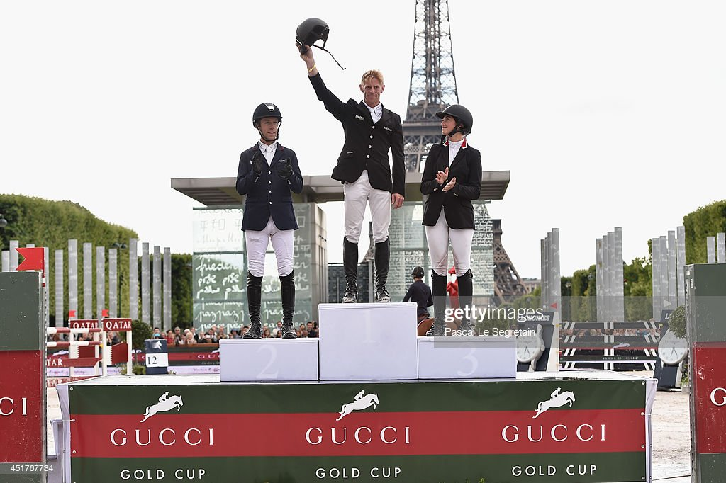 Winners of the 'Gucci Gold Cup Paris Eiffel Jumping Table A against the clock with jump-off ' Maikel van der Vleuten (2nd rank), Marcus Ehning (1st rank) and Reed Kessler (3rd rank) aknowledge the applause of the audience during the Paris Eiffel Jumping presented by Gucci at Champ-de-Mars on July 6, 2014 in Paris, France.