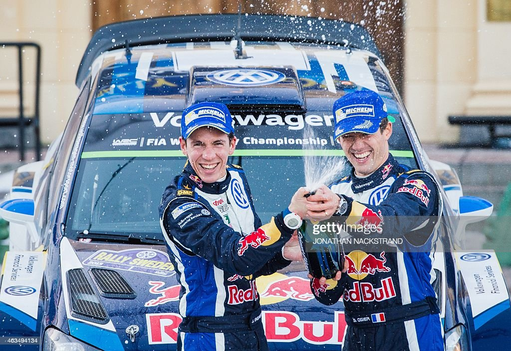 Winners Sebastien Ogier of France and his codriver Julien Ingrassia of France spray champagne next to their Volkswagen Polo R WRC during the winners...