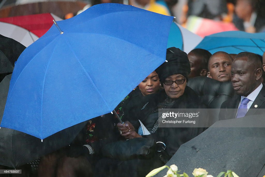 Winnie MadikizelaMandela sits under an umbrella during the official memorial service for former South African President Nelson Mandela at the FNB...