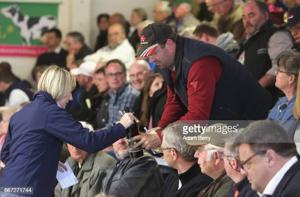 A winning bidder receives a bottle of local cherry wine after agreeing to purchase a heifer for at least 2500 euros the minimum amount required to...