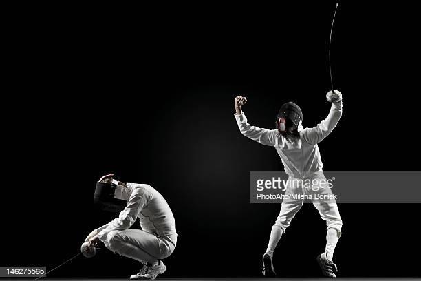 Winning fencer celebrating over defeated fencer