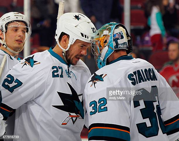 Winning goaltender Alex Stalock of the San Jose Sharks is congratulated by Scott Hannan after defeating the New Jersey Devils at the Prudential...