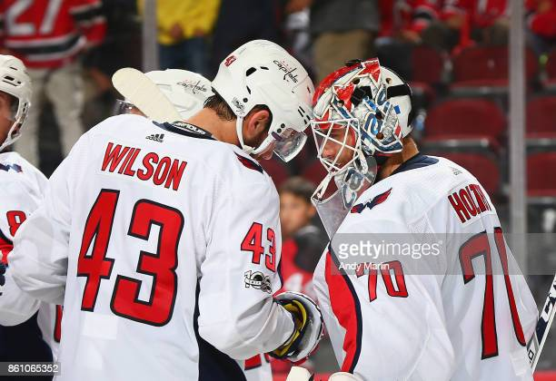 Winning goaltender Braden Holtby of the Washington Capitals is congratulated by Tom Wilson after defeating the New Jersey Devils at Prudential Center...