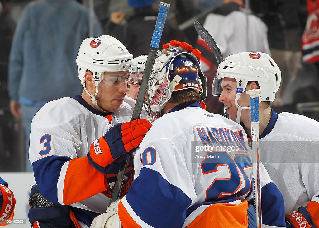 Winning goaltender Evgeni Nabokov #20 of the New York Islanders is congratulated by Travis Hamonic #3 after defeating the New Jersey Devils in overtime at the Prudential Center on January 31, 2013 in Newark, New Jersey. the Islanders defeated the Devils 5-4 in overtime.