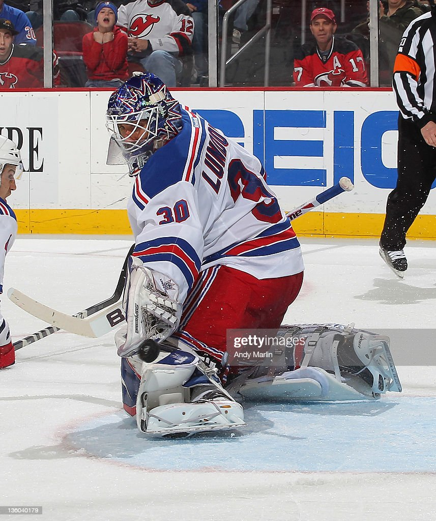 Winning goaltender <a gi-track='captionPersonalityLinkClicked' href=/galleries/search?phrase=Henrik+Lundqvist&family=editorial&specificpeople=217958 ng-click='$event.stopPropagation()'>Henrik Lundqvist</a> #30 of the New York Rangers eyes the puck after making a save against the New Jersey Devils at the Prudential Center on December 20, 2011 in Newark, New Jersey. The Rangers defeated the Devils 4-1.
