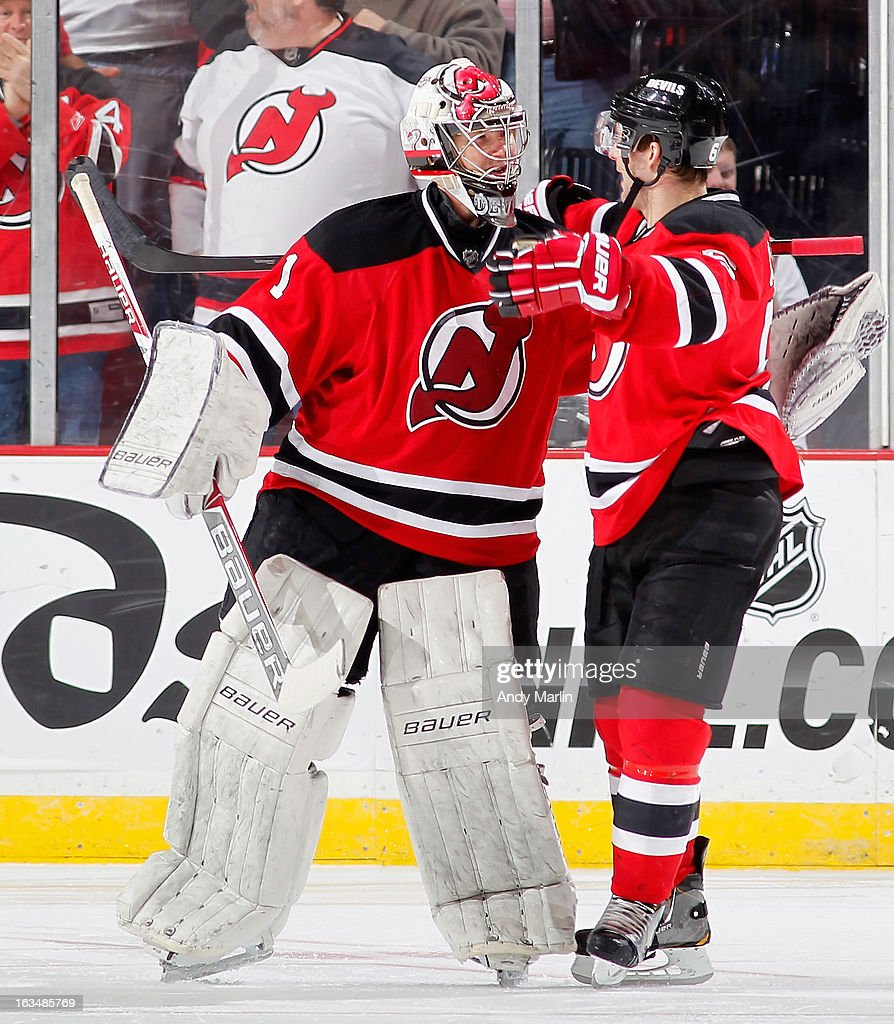 Winning goaltender Johan Hedberg #1 of the New Jersey Devils is congratulated by Andy Greene #6 after defeating the Winnipeg Jets in a shootout at the Prudential Center on March 10, 2013 in Newark, New Jersey. The Devils defeated the Jets 3-2 in a shootout.