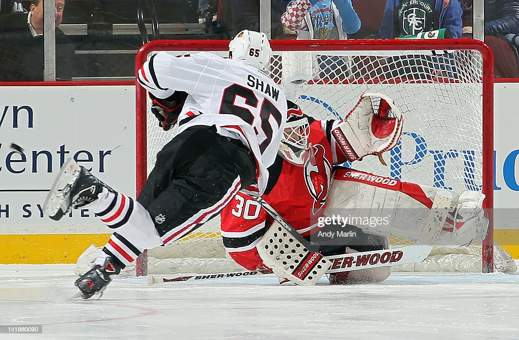 Winning goaltender <a gi-track='captionPersonalityLinkClicked' href=/galleries/search?phrase=Martin+Brodeur&family=editorial&specificpeople=201594 ng-click='$event.stopPropagation()'>Martin Brodeur</a> #30 of the New Jersey Devils makes a save against Andrew Shaw #65 of the Chicago Blackhawks to secure the shootout victory during the game at the Prudential Center on March 27, 2012 in Newark, New Jersey. The Devils defeated the Blackhawks 2-1 in a shootout.