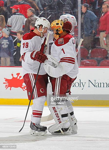 Winning goaltender Thomas Greiss of the Phoenix Coyotes is congratulated by Shane Doan after defeating the New Jersey Devils in a shootout at the...