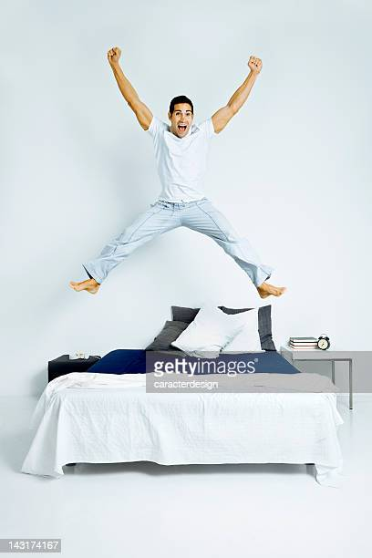 Winning man jumping on bed