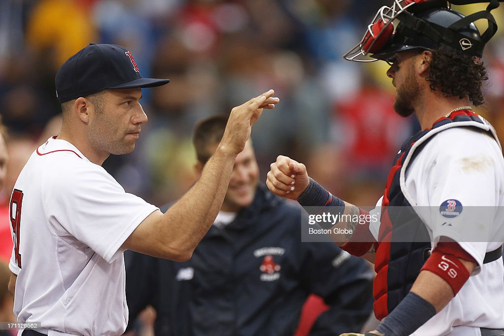 Winning pitcher, Alfredo Aceves (#91) greets catcher Jarrod Saltalamacchia (#39) at the dugout as the Boston Red Sox play the Tampa Bay Rays in a regular season MLB game at Fenway Park on Tuesday, June 18, 2013.