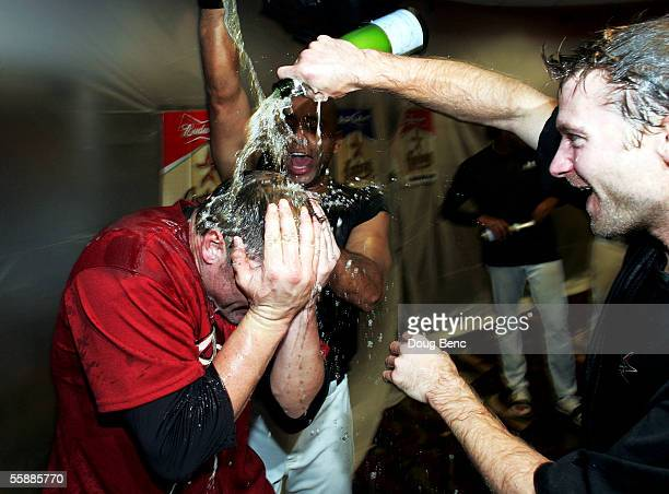 Winning pitcher Roger Clemens of the Houston Astros is doused with champagne in the locker room by teammates Jose Vizcaino and Adam Everett after...