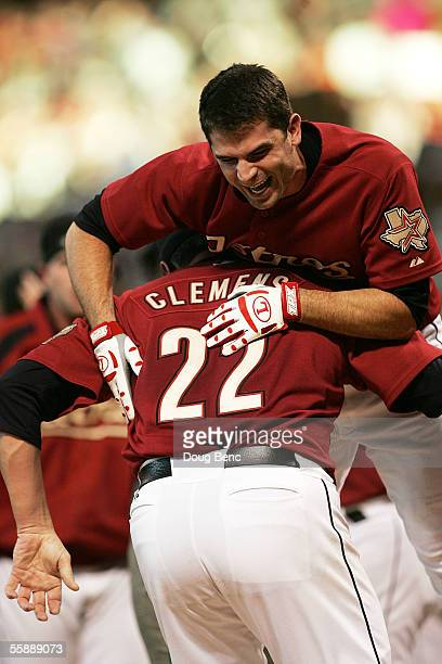 Winning pitcher Roger Clemens of the Houston Astros picks up Chris Burke to celebrate after Burke hit a solo home run to defeat the Atlanta Braves in...