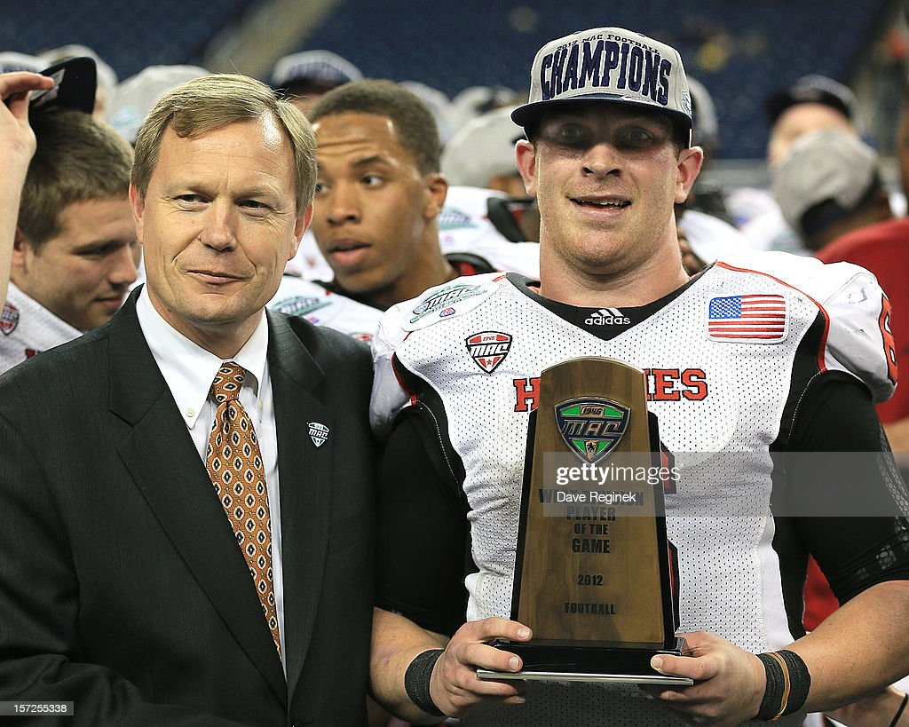 Winning quarterback Jordan Lynch #6 of the Northern Illinois Huskies is presented with the Player of the Game trophy from MAC Commissioner Dr. Jon A. Steinbrecher after defeating the Kent State Golden Flashes 44-37 during the Mid-American Conference Championship game at Ford Field on November 30, 2012 in Detroit, Michigan.