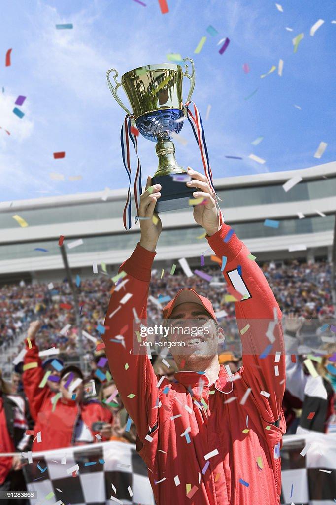 Winning race car driver holding trophy.