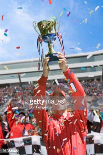 Winning race car driver holding trophy. : ストックフォト